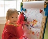 在画架的年轻女婴图画 免版税库存图片