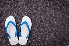 在黑柏油路的白色塑料触发器鞋子 库存照片