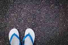 在黑柏油路的白色塑料触发器鞋子 库存图片