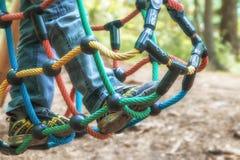 在绳索栅格的儿童的脚 图库摄影