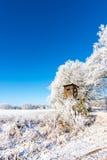 在冻树旁边的木棕色狩猎隐藏处 库存照片