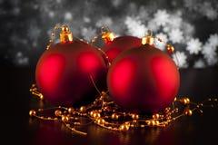 在黑桌上的三个红色圣诞节中看不中用的物品 免版税库存照片