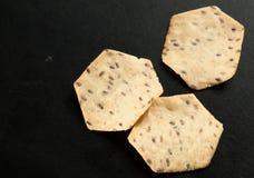 在黑桌上的三个金黄有机五谷薄脆饼干 免版税库存图片