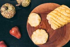 在黑桌上的切的新鲜的菠萝 库存照片