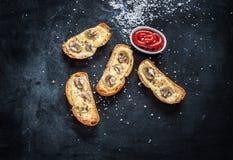 在黑桌上的被烘烤的乳酪bruschetta多士 免版税图库摄影