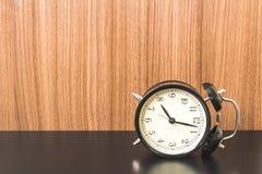在黑桌上的闹钟 图库摄影