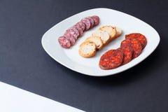 在黑桌的西班牙加调料的口利左香肠塔帕纤维布 库存图片