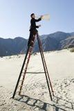 在活梯的商人使用扩音机在沙漠 免版税库存照片