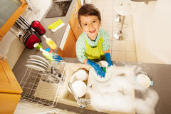 在水槽的小男孩洗涤的盘顶视图  库存图片