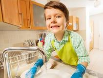 在水槽的小男孩洗涤的盘画象  库存照片
