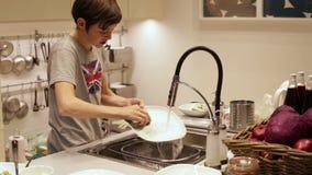 在水槽的少年男孩洗涤的盘 影视素材