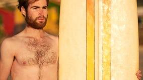 在水橇板旁边的坚固性有胡子的男性冲浪者画象 免版税库存照片