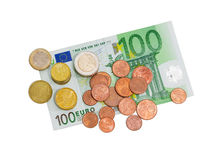 在100欧元钞票背景的欧洲硬币  库存图片