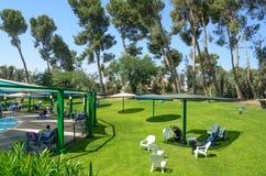 在水池、遮阳伞和塑料椅子附近的绿草草坪室外休闲的 免版税库存图片