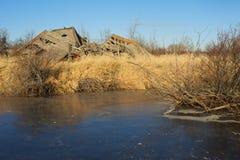 在冻池塘附近的烂掉老谷仓 图库摄影