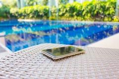 在水池旁边的扶手椅子上把放的智能手机 免版税库存图片