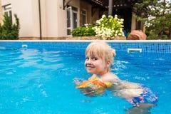 在水池的一点逗人喜爱的白肤金发的女孩游泳,佩带的可膨胀的袖子 她是微笑和愉快的 免版税库存照片