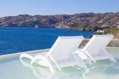 在水池的两张白色海滩睡椅有海视图在希腊 免版税图库摄影