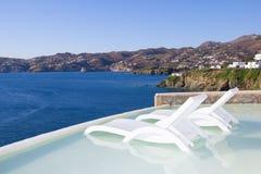在水池的两把白色椅子有海视图在希腊 免版税图库摄影