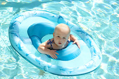 在水池的俏丽的女婴游泳在小船 库存照片