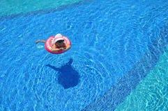 在水池的小女孩游泳在可膨胀的圆环 免版税库存图片
