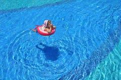 在水池的小女孩游泳在可膨胀的圆环 免版税库存照片