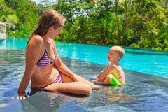 在水池的愉快的儿童游泳与母亲 免版税库存图片