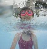 在水池的愉快的小女孩游泳 免版税库存照片