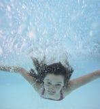 在水池的愉快的小女孩游泳 免版税库存图片