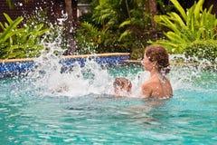 在水池的母亲和儿子游泳 免版税库存图片