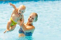 在水池的母亲和婴孩游泳 免版税图库摄影