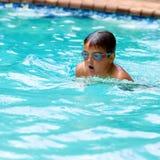 在水池的男孩实践的蛙泳。 库存照片