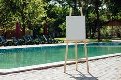 在水池的白色空的画架 库存照片
