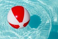 在水池的红色和白色海滩球 库存图片