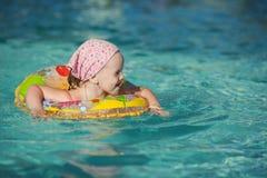 在水池的美好的矮小的快乐的女孩游泳 库存照片