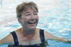 在水池的资深妇女游泳 库存照片