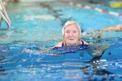 在水池的资深妇女游泳 免版税图库摄影