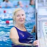 在水池的资深妇女游泳 图库摄影
