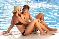 在水池的边缘的有吸引力的夫妇 图库摄影