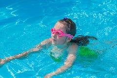 在水池的逗人喜爱的女孩游泳 库存照片