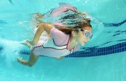 在水池的逗人喜爱的孩子游泳 免版税图库摄影