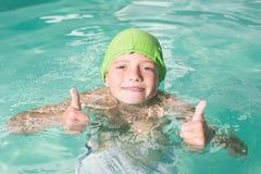 在水池的逗人喜爱的孩子游泳 库存照片