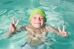 在水池的逗人喜爱的孩子游泳 免版税库存照片