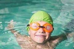 在水池的逗人喜爱的孩子游泳 免版税库存图片
