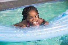 在水池的逗人喜爱的小女孩游泳 免版税库存图片