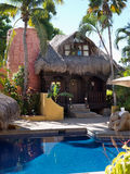 在水池附近的豪华palapa屋顶平房 图库摄影