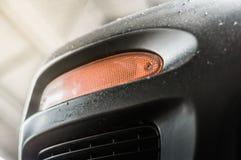 在黑汽车的橙色转弯信号 库存图片