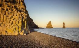 在黑沙子海滩与巨大的峭壁,冰岛的美好的日落 免版税库存照片