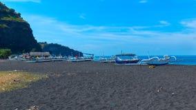 在黑沙子海滩的小船  图库摄影