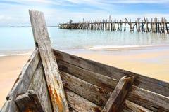 在黑沙子海滩的老小船 免版税库存图片